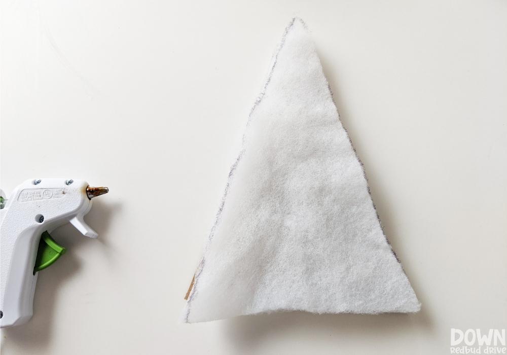 A piece of quilt batting being glued to a triangular piece of cardboard.