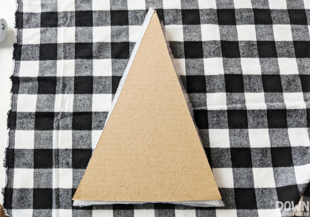 The triangular cardboard and quilt batting sitting on a piece of black and white buffalo check fabric.