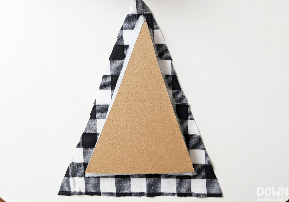 The buffalo check fabric cut into a triangle for the wood and fabric Christmas tree DIY.