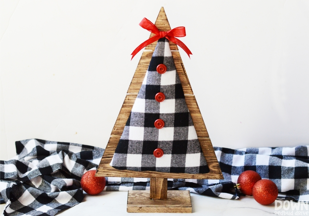 The finished wood and fabric Christmas tree DIY with red buttons and a bow added to it.