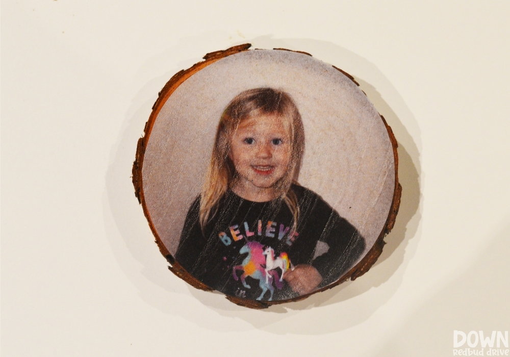A tissue paper picture applied to a wood slice ornament using Modge Podge.