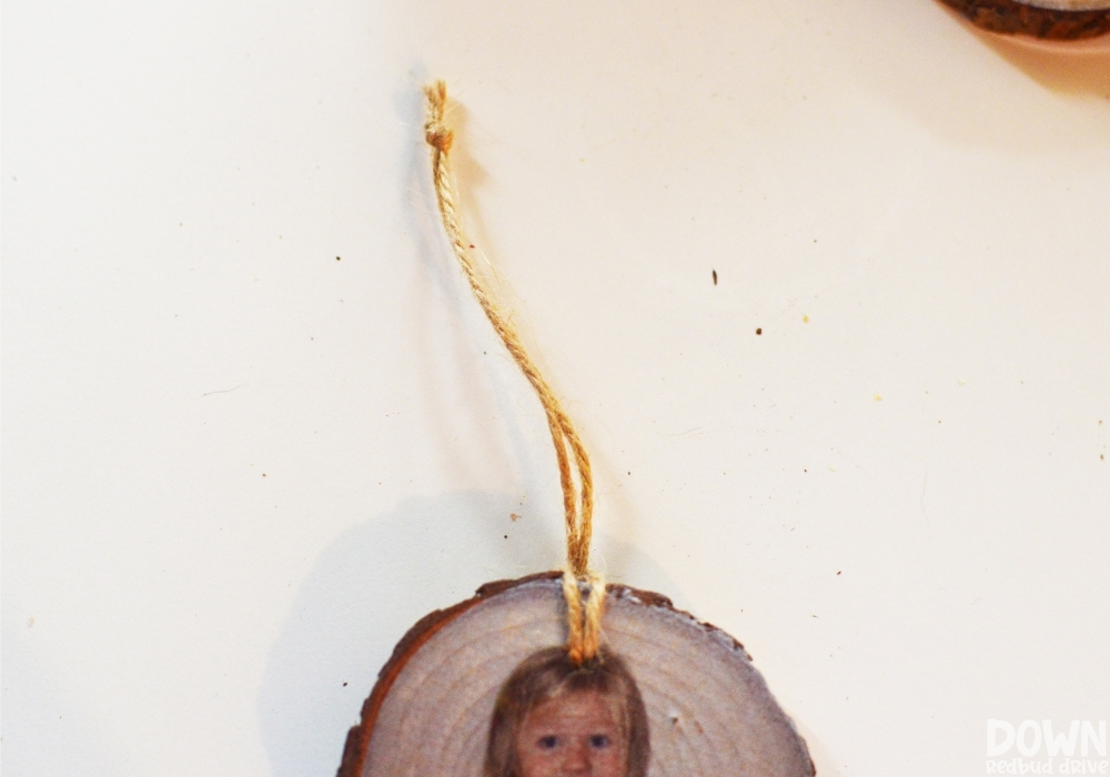 A piece of twine tied through the hole of the DIY Wood Photo Ornament in order to hang it.