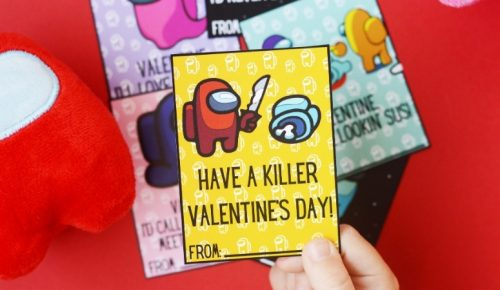 "A child holding an Among Us Valentine that says ""Have a killer Valentine's Day!"""