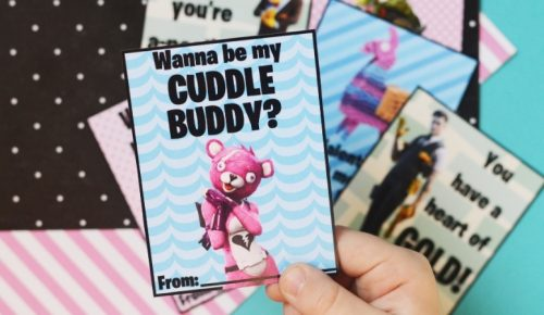 """A child holding a Fortnite valentine that says """"Wanna be my cuddle buddy?"""" on it."""
