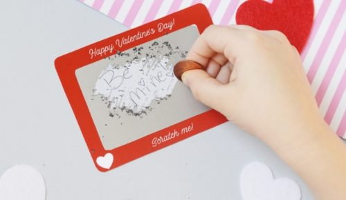 "A wide closeup of a Scratch Off Valentine that says ""Be mine!"""