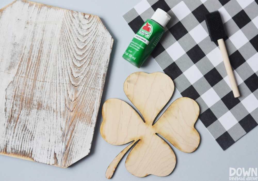Overhead view of the supplies for the DIY buffalo plaid shamrock sign.