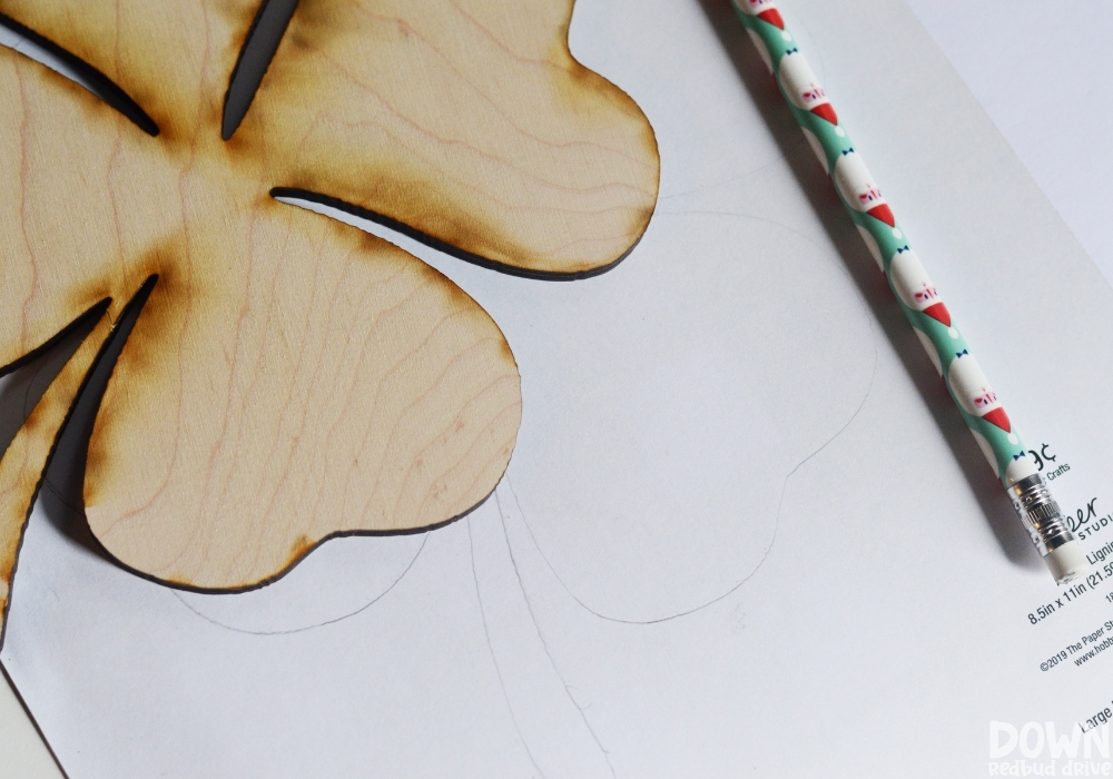 Overhead of a shamrock traced out on the back of buffalo plaid patterned paper.