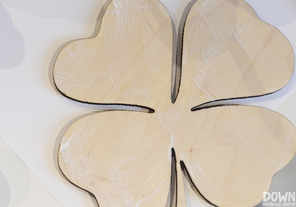 Overhead shot of mod podge applied to a wooden shamrock.