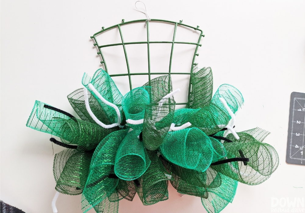 A hat wreath base with green rolled mesh attached with pipe cleaners.