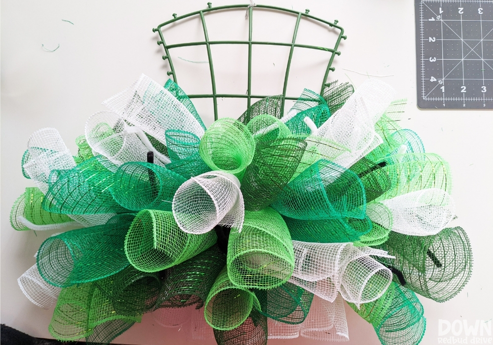 Green and white mesh attached to a hat wreath base.