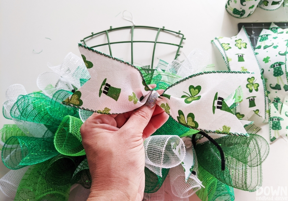 Showing how to pinch and hold ribbon to attach it to a mesh wreath.
