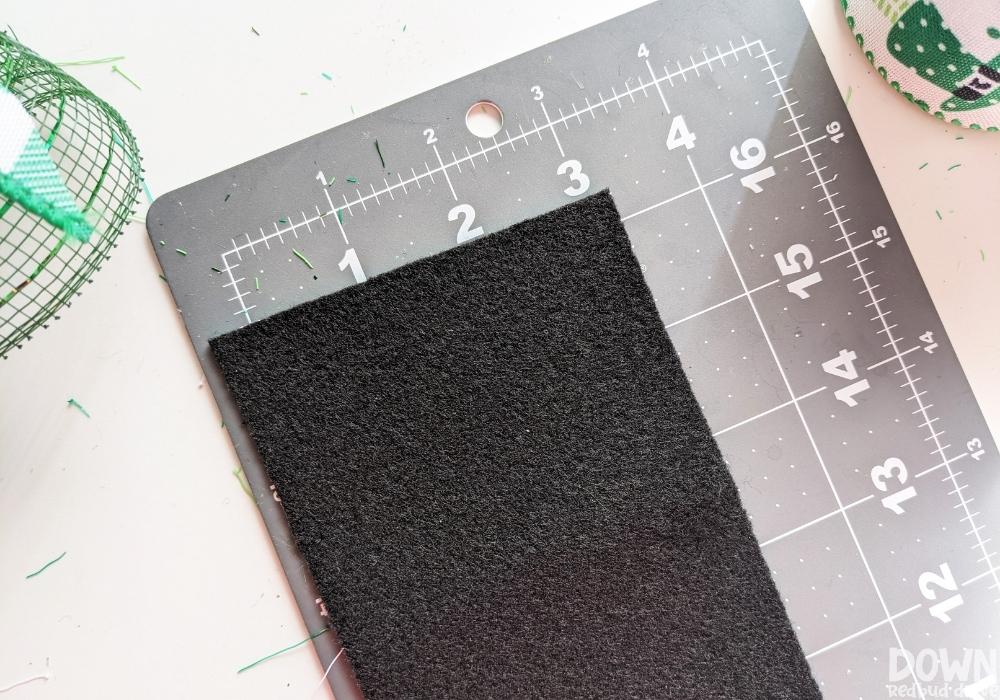 Using a cutting mat to measure and cut black felt.