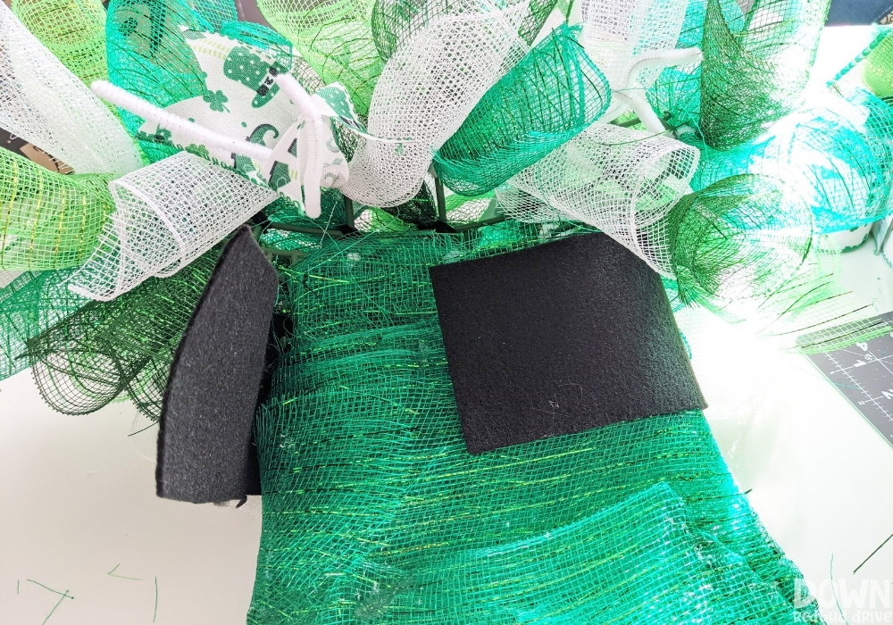 Attaching the black band to the top of a mesh hat wreath.