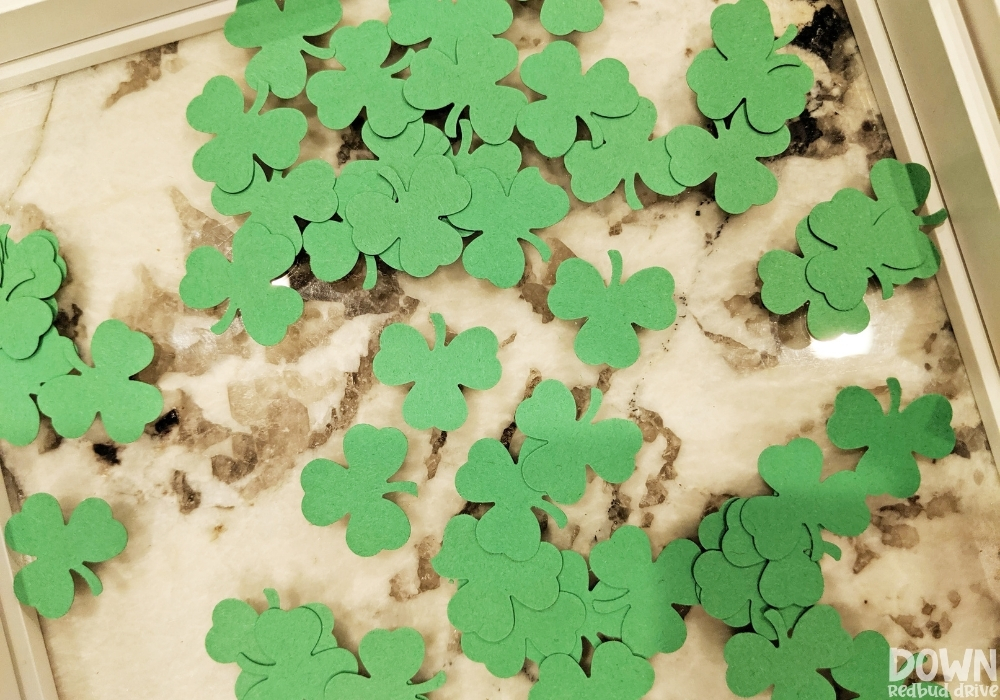 Overhead view of filling the art frame with shamrock part cut outs.