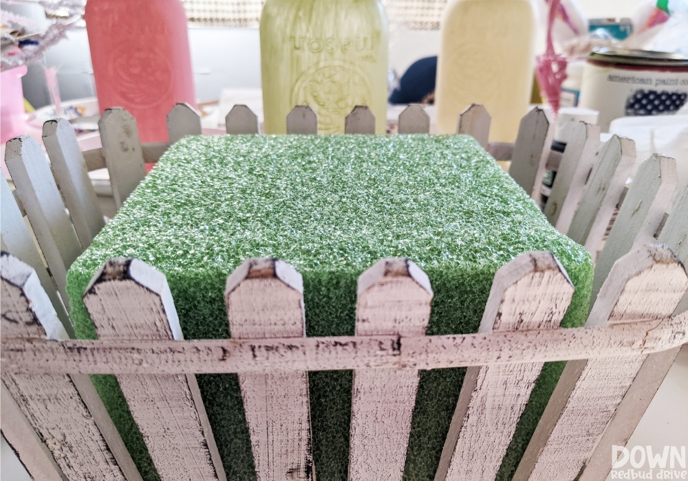 A piece of green floral foam placed inside a white picket fence basket.