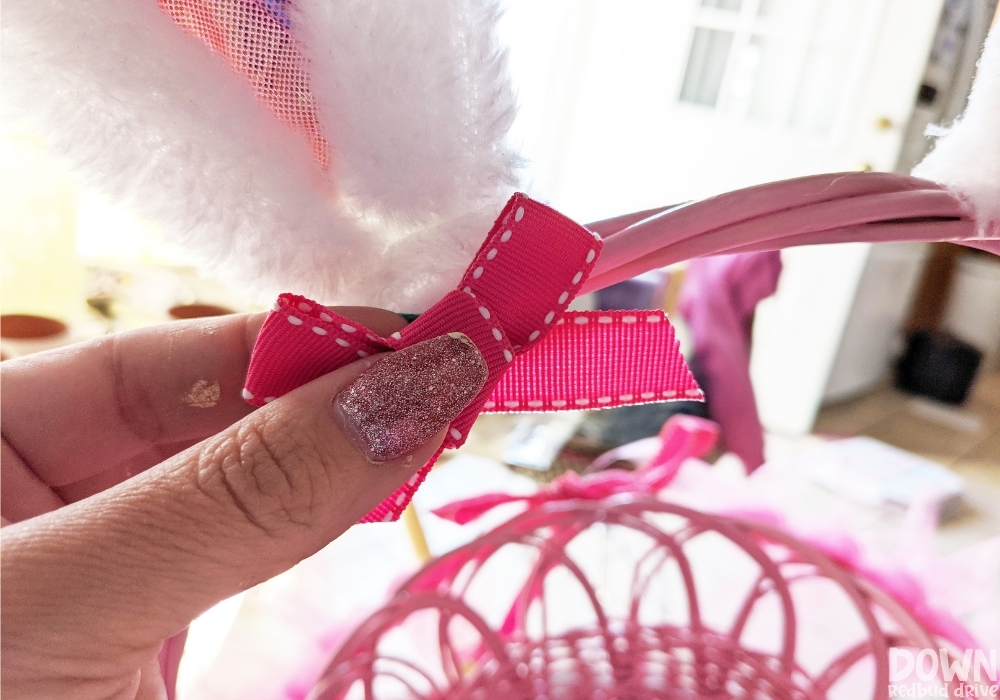 A pink bow for the DIY Easter basket decoration.