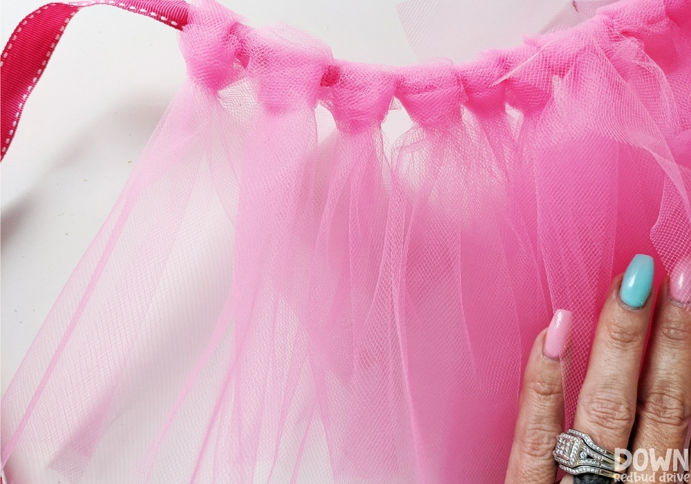 Tulle tied in slip knots on a pink ribbon to make a homemade tutu.
