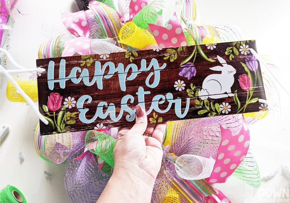 """Close up of the """"Happy Easter"""" sign with pipe cleaners threaded through holes on all four corners for attaching it to the DIY Easter mesh wreath."""