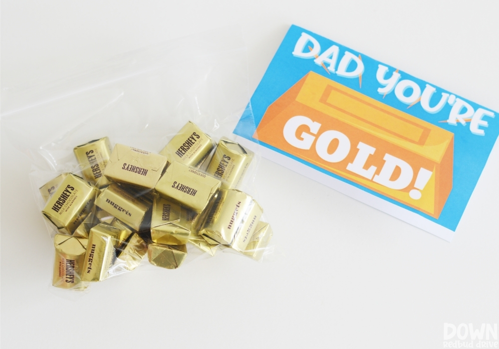 """Close up of a bag of Hershey's Gold Nuggets next to a printable tag that says """"Dad You're Gold!"""""""