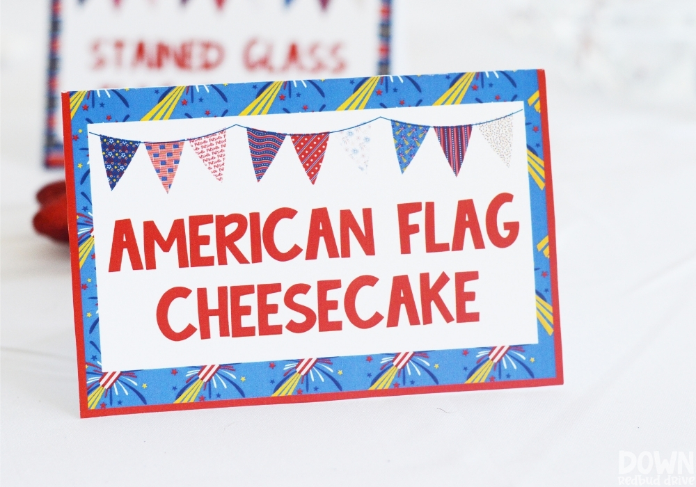 """Closeup of a 4th of July party food card for """"American Flag Cheesecake""""."""