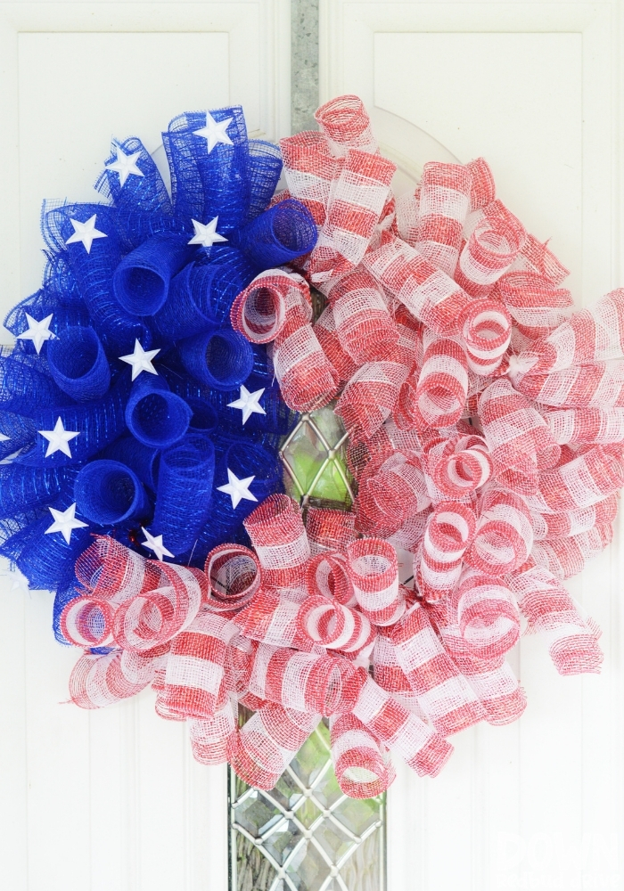 Tall shot of the finished DIY American Flag Mesh Wreath on a white door.