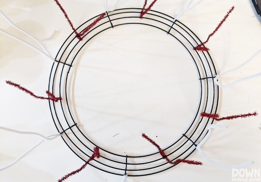 Overhead view of red and white chenille stem pipe cleaners attached to a wreath form.