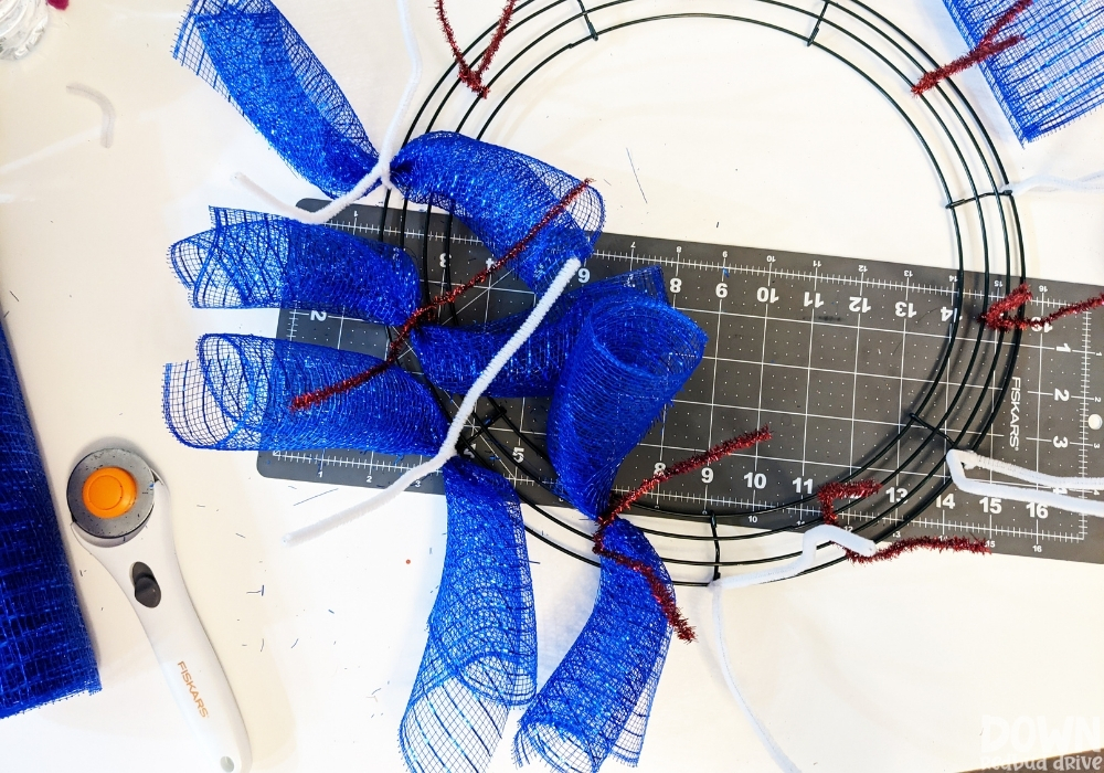 Overhead view of blue deco mesh being attached to a wreath form.