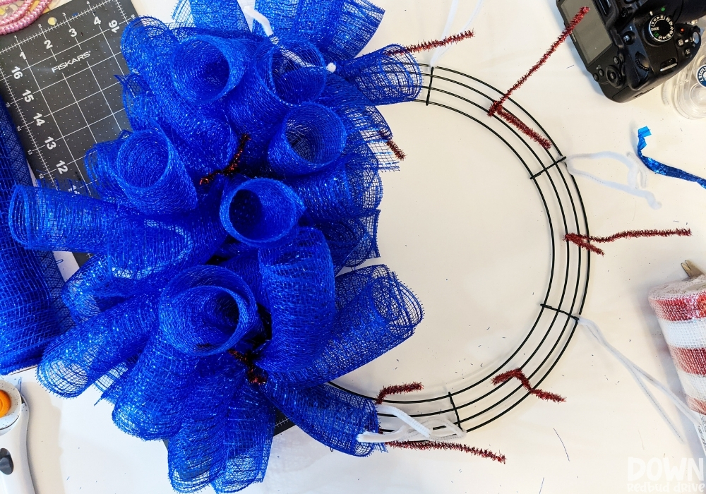 Overhead view of half of a wreath form covered in blue deco mesh.