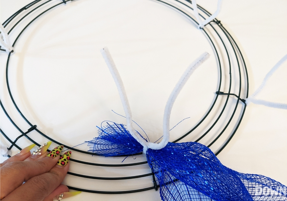 A piece of deco mesh attached to a wreath form with a chenille stem pipe cleaner.
