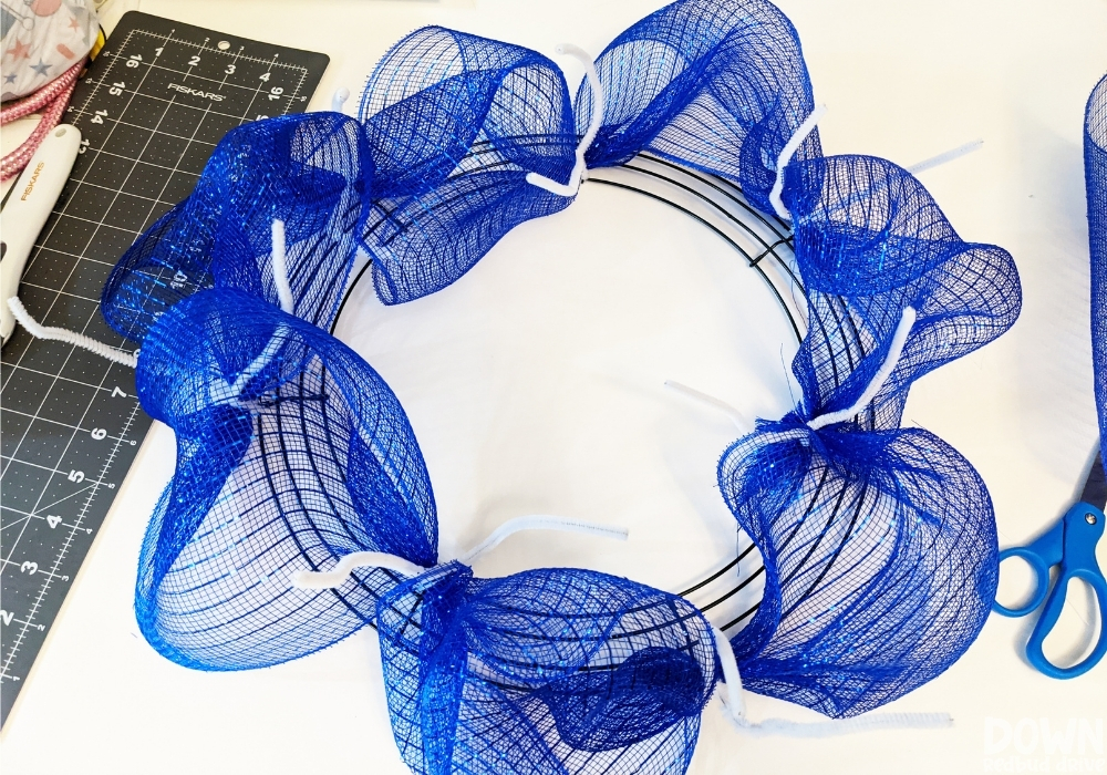 Blue deco mesh attached to a wreath form with white chenille stem pipe cleaners.