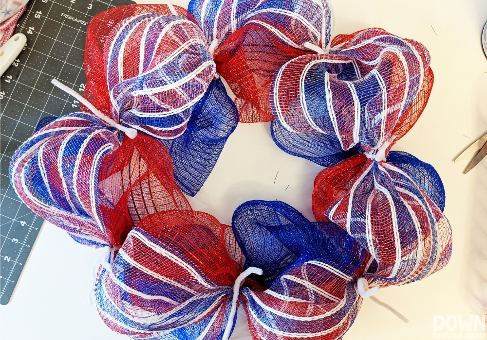Red and white stripped deco mesh added to a wreath form for the Patriotic Deco Mesh Wreath.