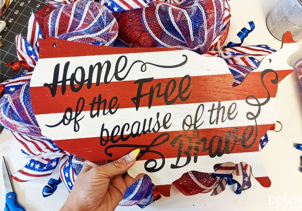 """A sign in the shape of the United States that says, """"Home of the free because of the brave""""."""
