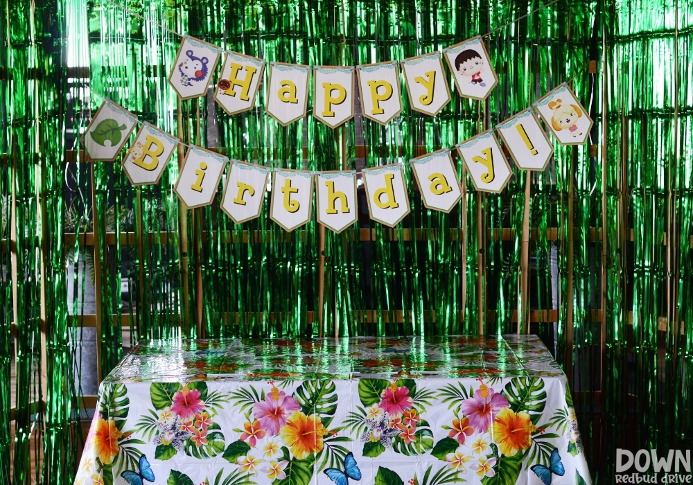 """A printable Animal Crossing """"Happy Birthday"""" banner over a tropical themed gift table."""