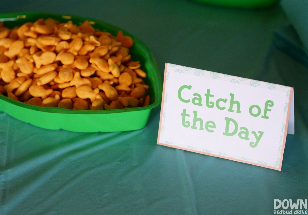 """Closeup up of the """"Catch of the Day"""" food card with goldfish crackers next to it."""