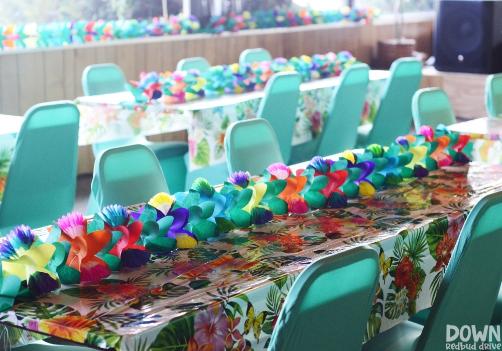 A flower centerpiece laying on a tropical themed table cloth.