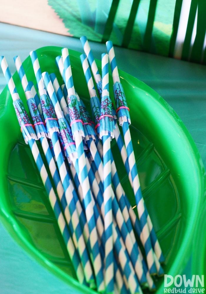 Umbrella straws sitting in a leaf shaped bowl.