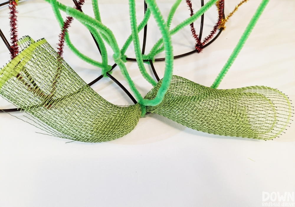 Green deco mesh attached to a pumpkin wreath form with green pipe cleaners.