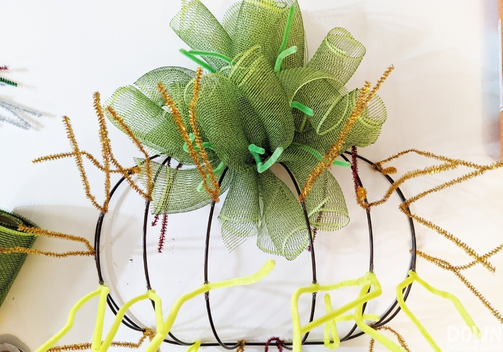 The green deco mesh finished being attached to the wreath form for the DIY Mesh Pumpkin Wreath.