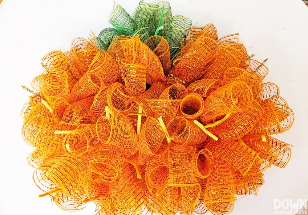 The orange deco mesh done being attached for the DIY Mesh Pumpkin Wreath.
