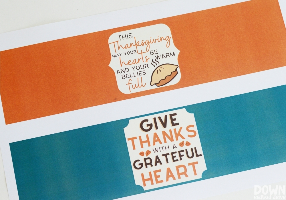 """Closeup of printable candle tags that say """"This Thanksgiving may your hearts be warm and your bellies full"""" and """"Give thanks with a grateful heart""""."""