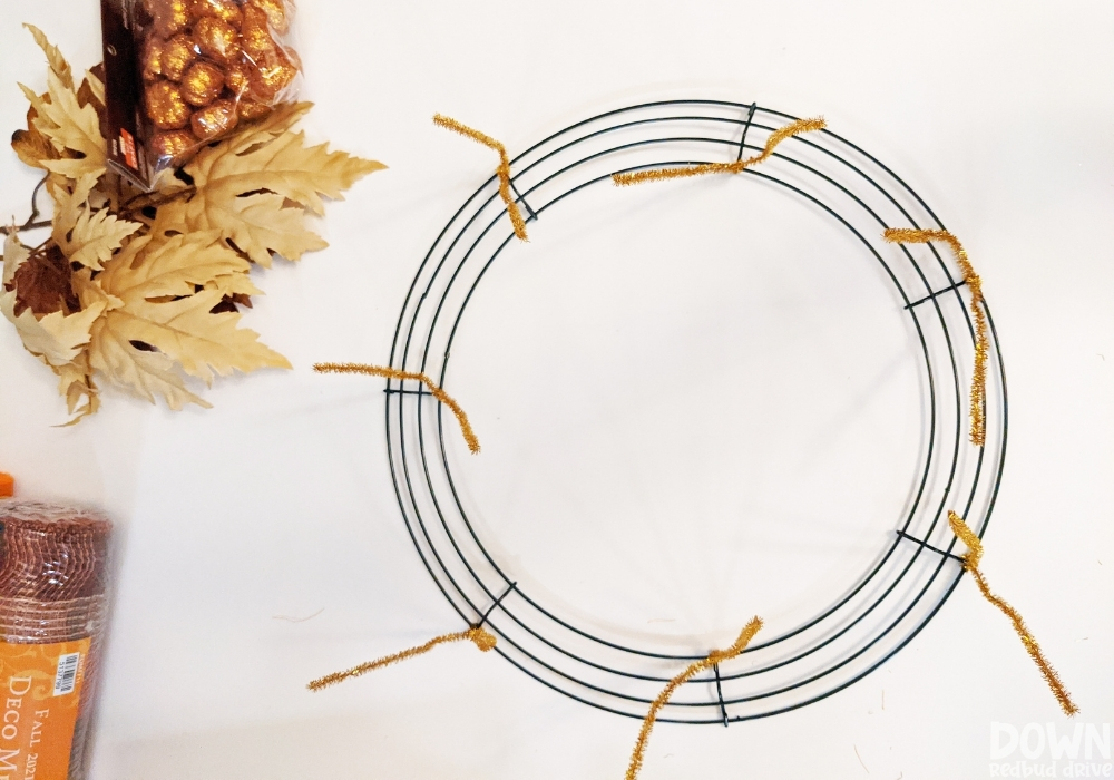 Gold pipe cleaners attached to a wire wreath form.
