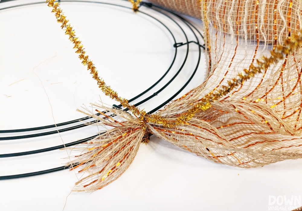 Closeup of fall colored deco mesh being attached to a wreath form with pipe cleaners.