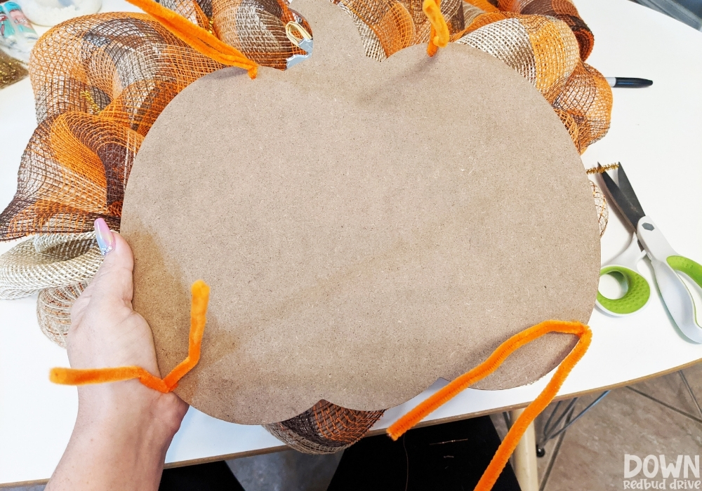 A fall pumpkin sign being attached to a wreath form with orange pipe cleaners.