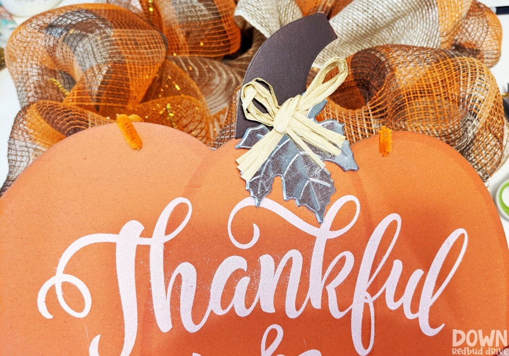 A close up of the pumpkin sign attached to a wreath form with orange pipe cleaners for the DIY Thanksgiving Mesh Wreath.