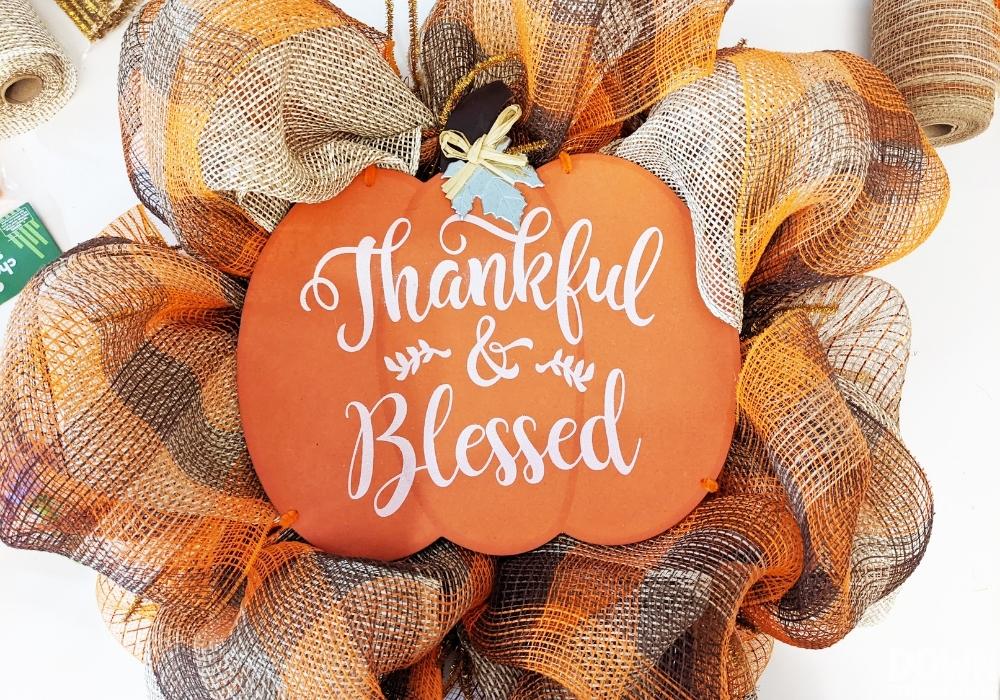 """A """"Thankful & Blessed"""" pumpkin sign attached to a fall deco mesh wreath."""