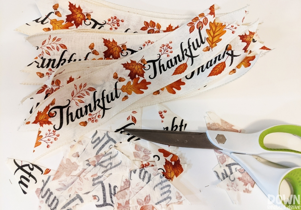 """Sections of """"Thankful"""" fall ribbon cut for the DIY Thanksgiving Mesh Wreath."""