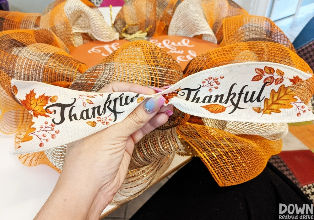 """The """"Thankful"""" ribbon pinched together to be attached to the DIY Thanksgiving Mesh Wreath."""