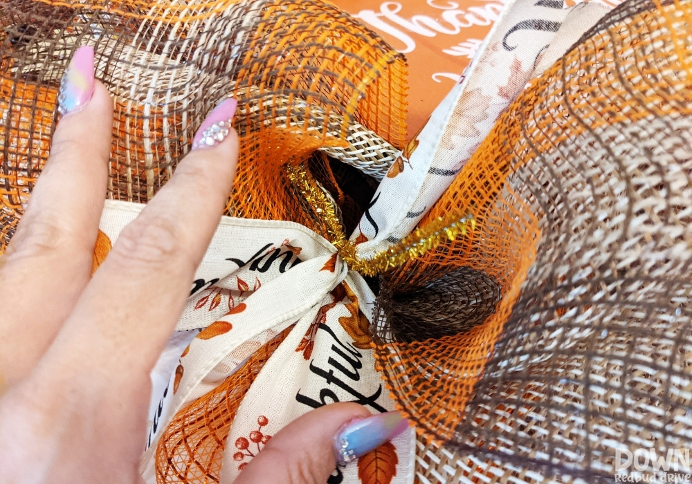 """Closeup of the """"Thankful"""" ribbons attached to the wreath form with gold pipe cleaners."""