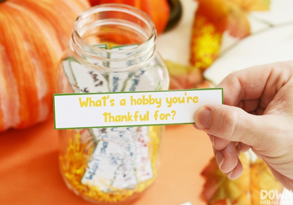 """A closeup of a hand holding the question """"What's a hobby you're thankful for"""" from the thanksgiving conversation starters game."""
