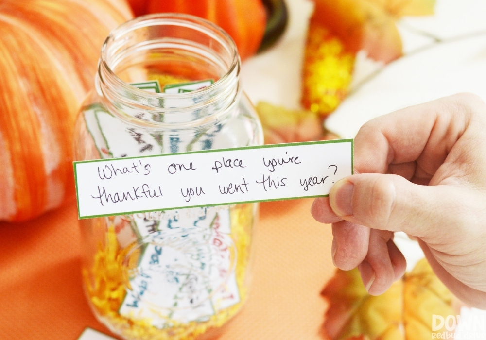 """A closeup of a hand holding the question """"What's one place you're thankful you went this year"""" from the thanksgiving conversation starters game."""